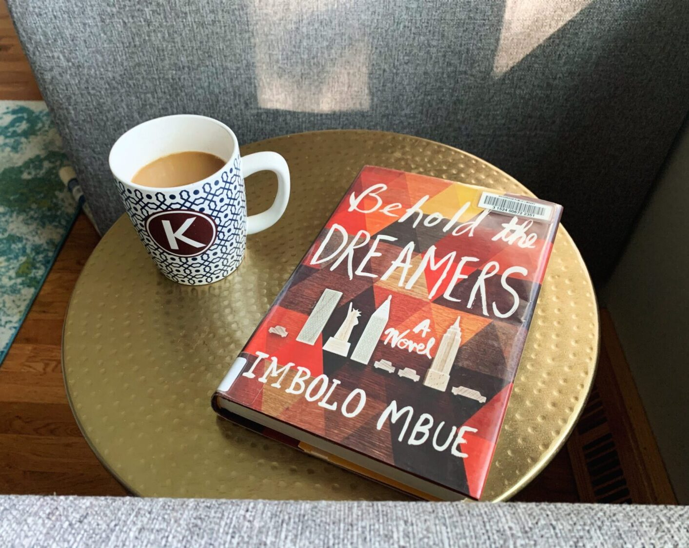 Coffee cup and Behold the Dreamers book in the sunshine. Part of my Sunday routine for success.