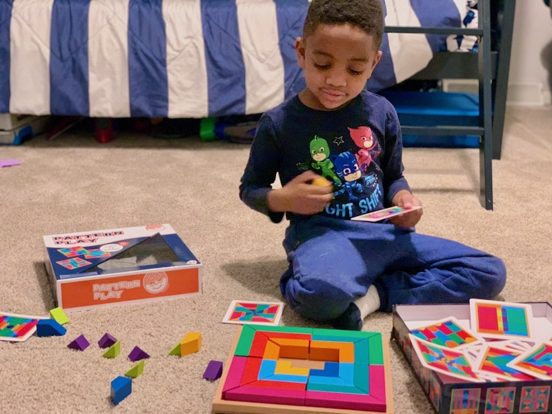 CLL playing with a brightly colored puzzle on the floor. Pattern puzzle for encouraging a pre-K child.