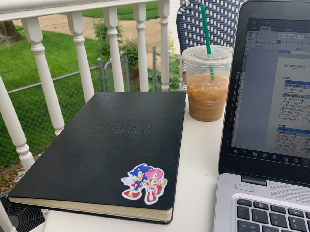 black bound notebook on a white table with Starbucks cup and a laptop. notebook has cartoon sticker on it.