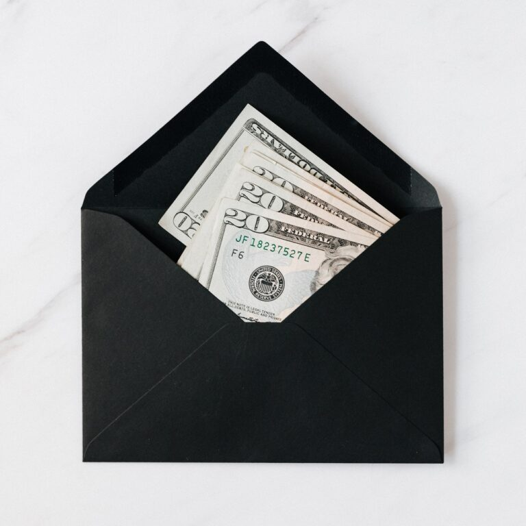 Black envelope on a white and gray background, containing multiple folded 20 dollar bills