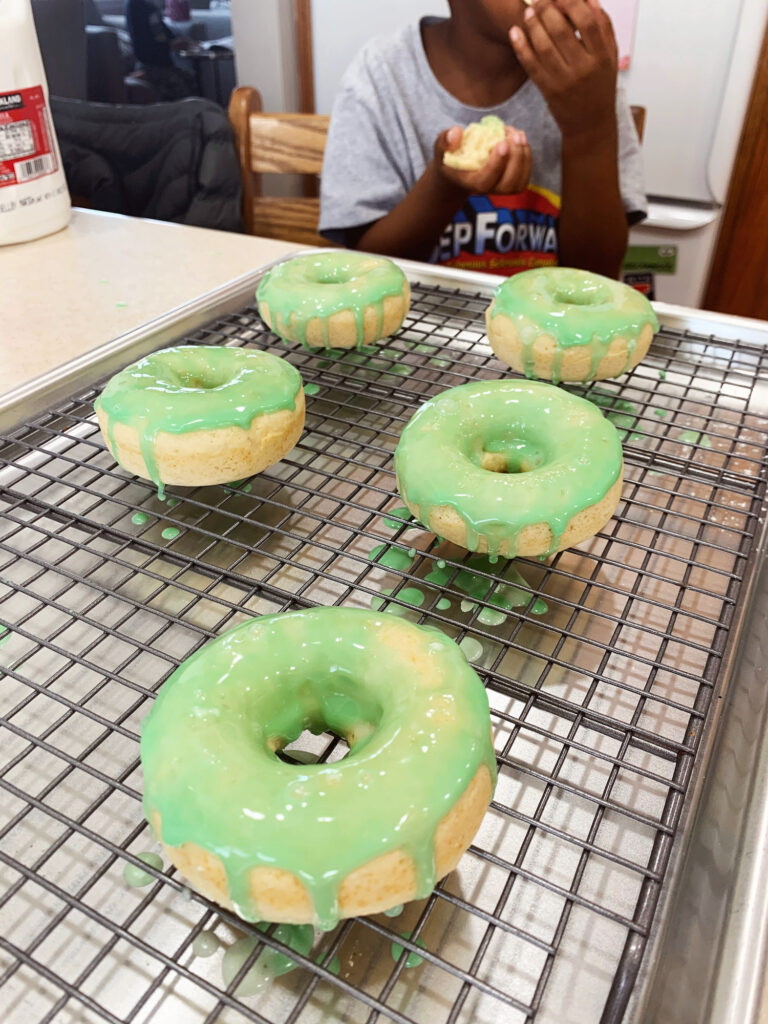 Five green glazed donuts on a cooling rack on a silver baking sheet