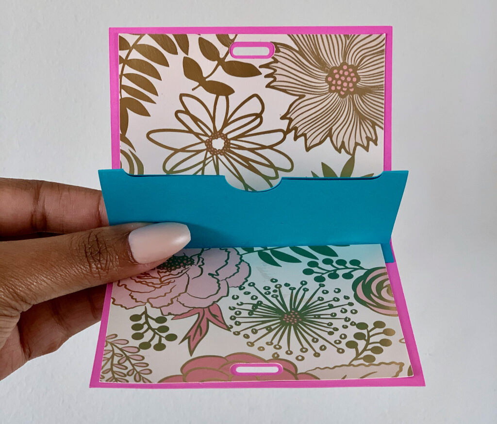 The inside of a teachers gift card holders made with Cricut machine. Pink and gold flowers on the card and the inside holder is blue.
