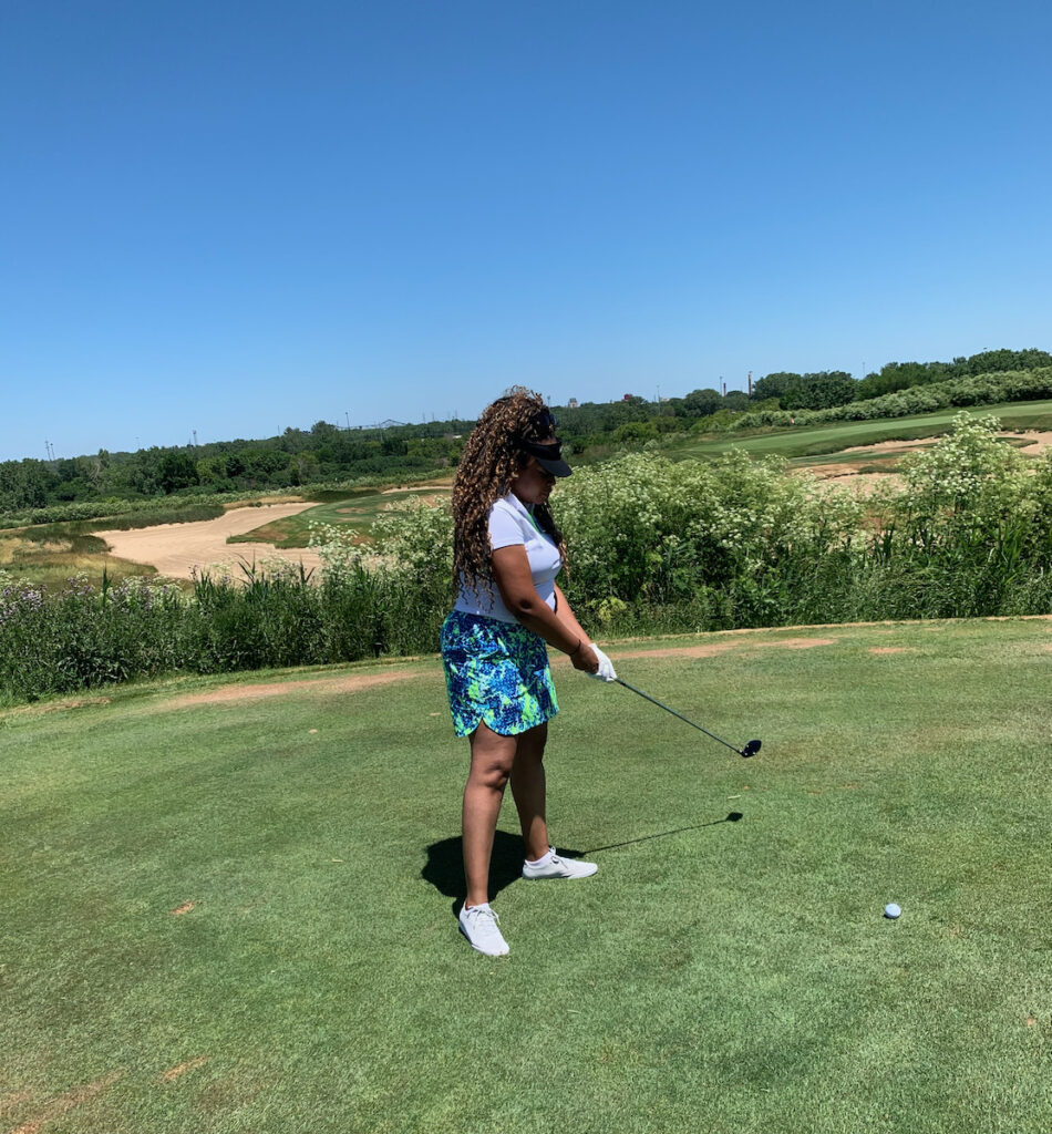 KBL holding golf club at an outdoor golf course