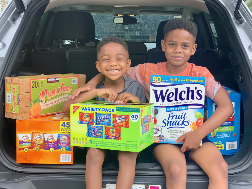 two boys smiling with snacks to help fight summer hunger