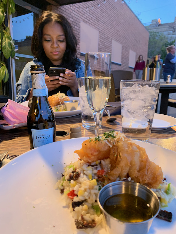 Dinner outside at Gentelin's during visit to Alton, Illinois. Woman in background while plate of food is in front.