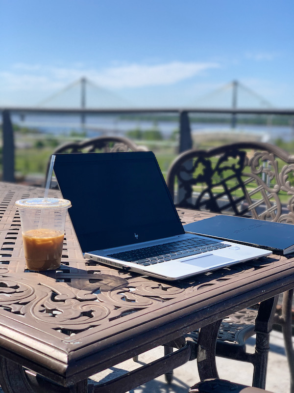 Laptop and iced coffee on outdoor deck overlooking river and bridge. Cracker Factory lodging during visit to Alton, Illinois
